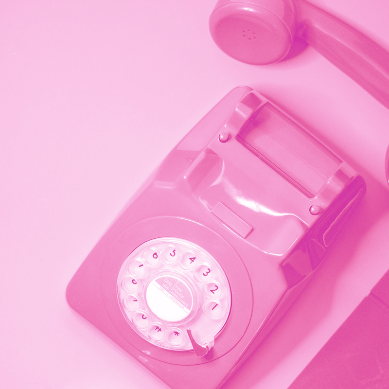 A hero image of a pink telephone supporting the article for '7 Reasons Online Live Chat Is Replacing Telephony'