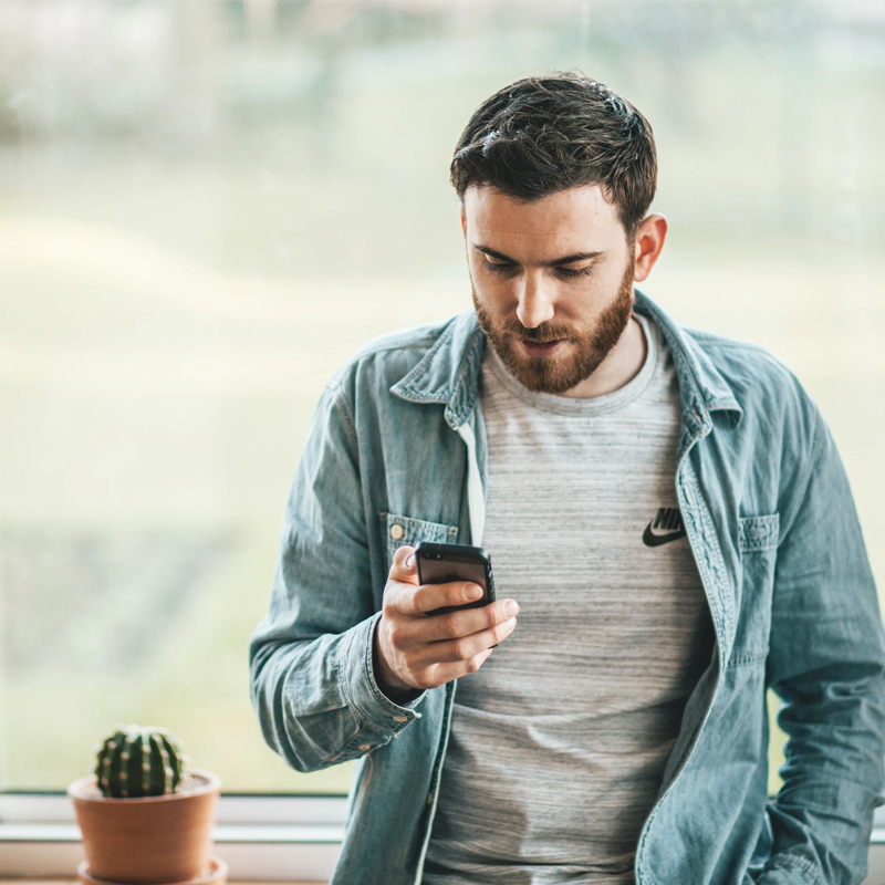 An image of a young man looking at his mobile phone to support article '5 Reasons Customers Prefer Live Chat (When It's Done Well)'